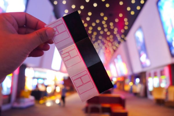 Young man's hand holding a paper ticket on blurred cinema complex background